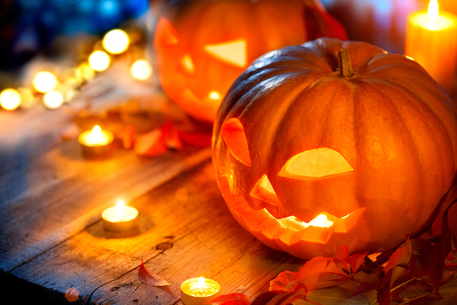Halloween+pumpkin+head+jack+lantern+with+burning+candles+over+wooden+background.+Halloween+holidays+art+design%2C+celebration.+Carved+Halloween+Pumpkins+with+burning+candles
